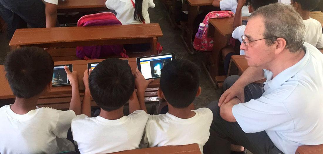 D. César Alierta junto con alumnos utilizando las tabletas de ProFuturo.